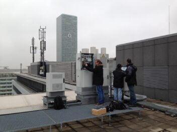Techniker arbeiten auf einem Dach an einer Basisstation. Im Hintergrund sind der O2-Tower und Antennen zu sehen