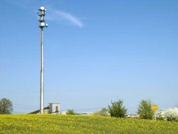Ein Mobilfunksendemast steht in einer ländlichen Region. Im Vordergrund ist eine Wiese in einer hügeligen Region zu sehen