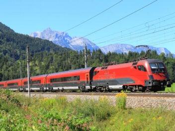 Railjet der österreichischen ÖBB vor Alpenpanorama.