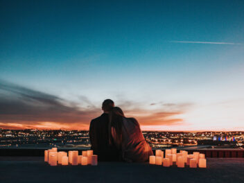 Ein Pärchen beobachtet einen Sonnenuntergang vor einer Stadt-Skyline.