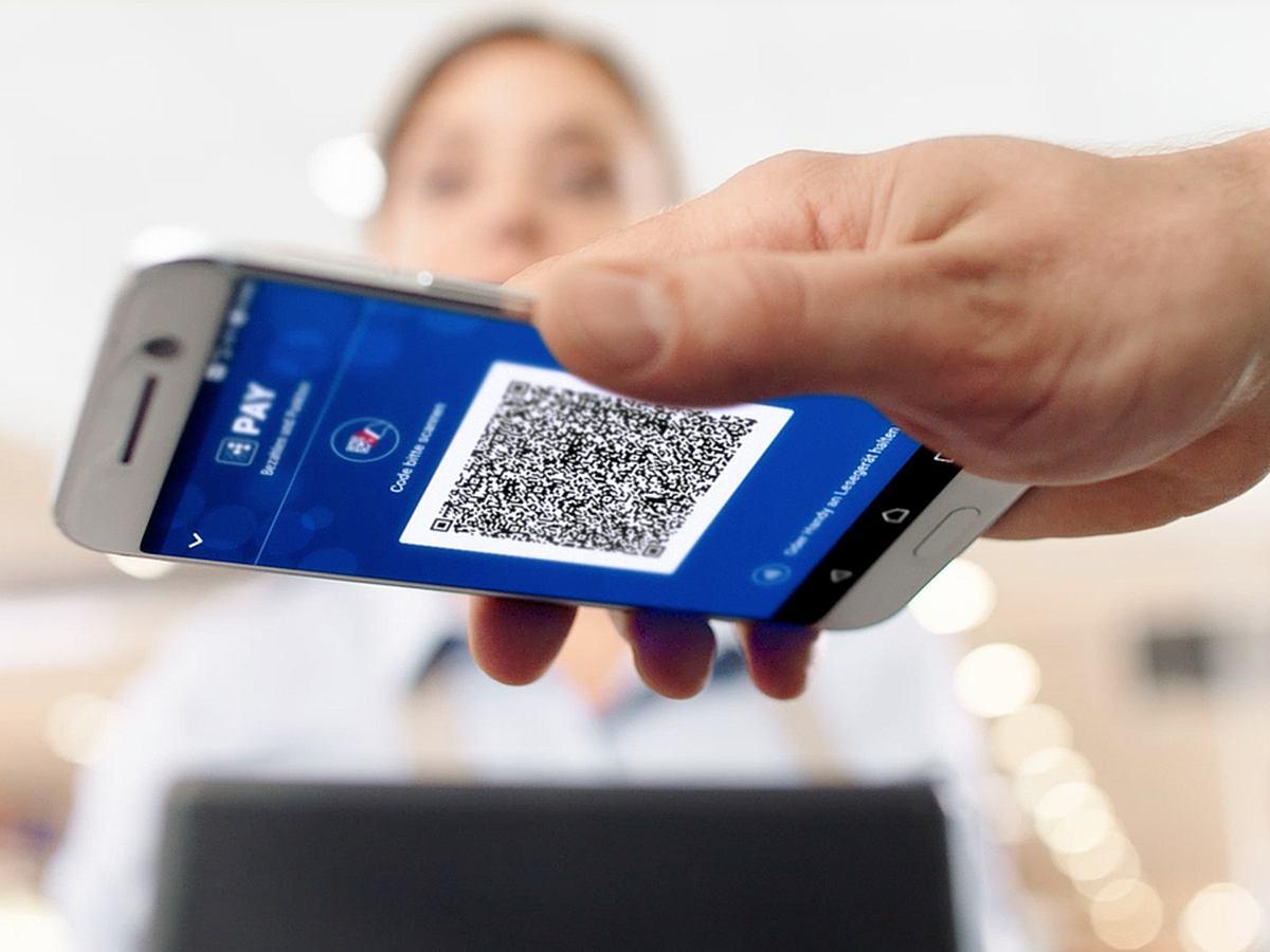 Ein Handy mit einem QR-Code wird über einen Scanner gehalten