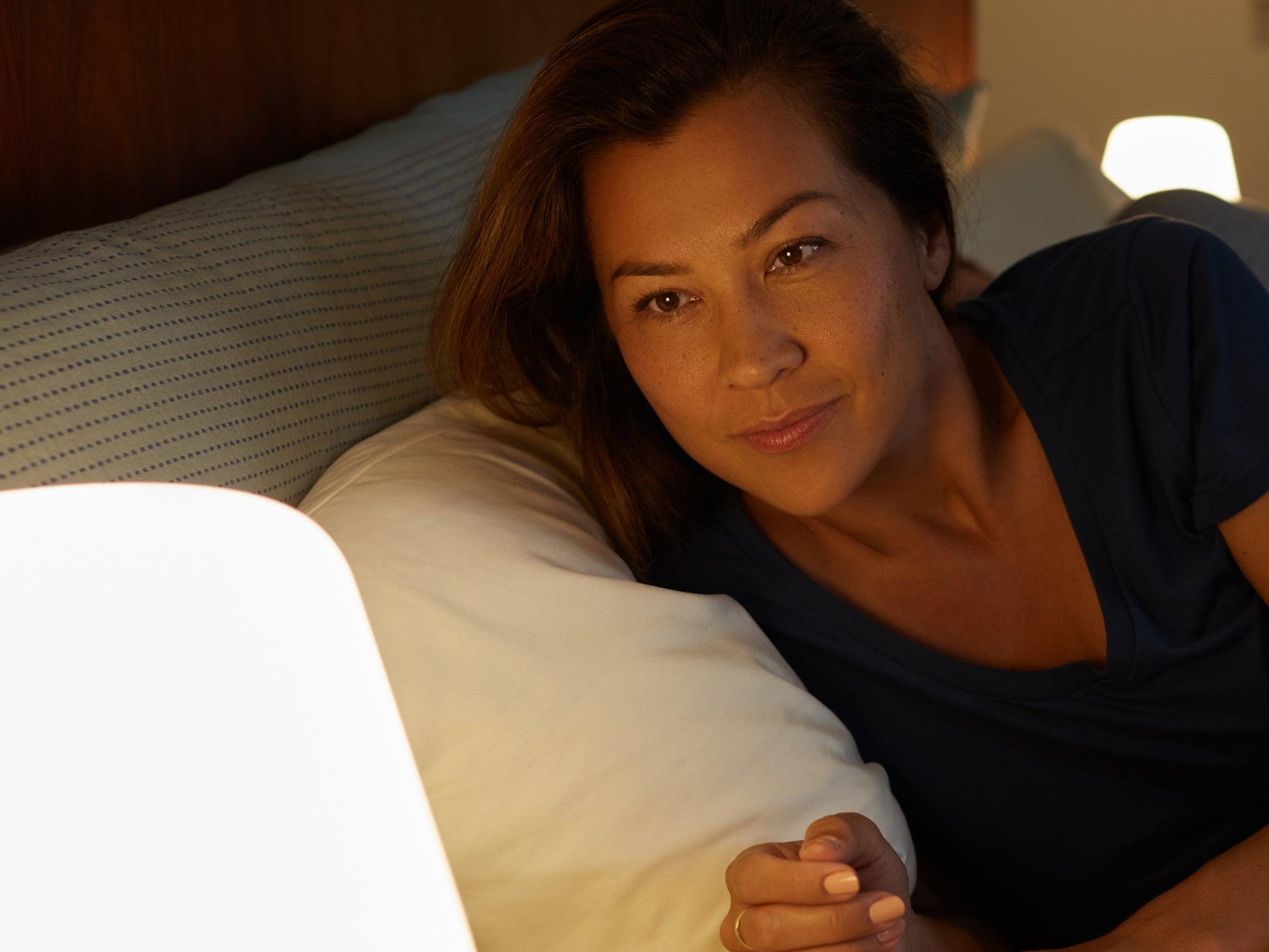 Frau im Bett schaut auf eine smarte Lampe