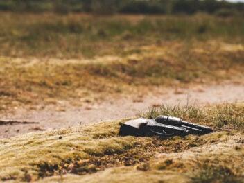 Pistole liegt im Sand auf dem Boden.