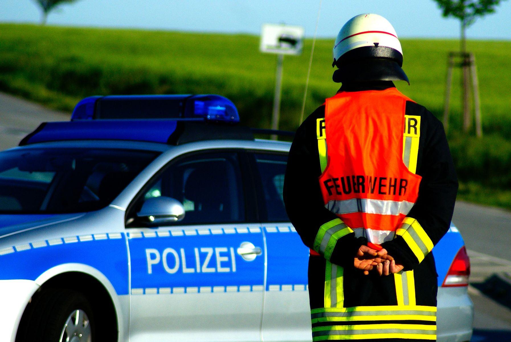 Ein Feuerwehrmann vor einem Polizei-Auto
