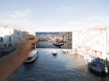 Eine Postkarte in einer Hand vor das fotografierte Motiv gehalten.