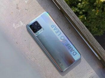 Die silbrige Rückseite des Realme 8 auf einem Metalluntergrund.
