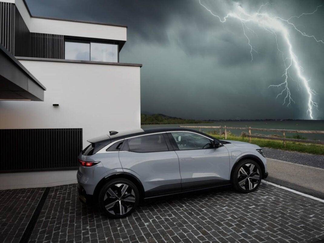 Renault Mégane E-Tech Electric steht vor einem Haus und im Hintergrund ist ein Blitz zu sehen.