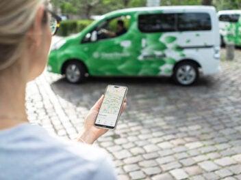 Eine Frau im Vordergrund hält ein Smarpthone mit einem Minibus im Hintergrund