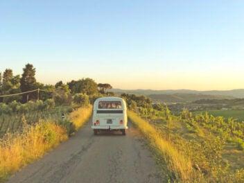 Ein Van fährt auf einer sandigen Straße entlang von Grün in den Sonnenuntergang