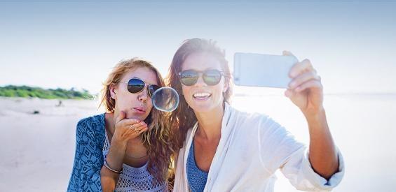 Zwei Mädchen mit Handy im Urlaub am Strand
