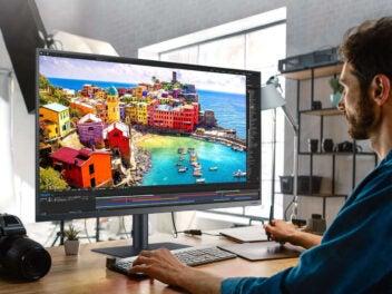 Mann sitzt vor einem Samsung-Monitor und bearbeitet Fotos.
