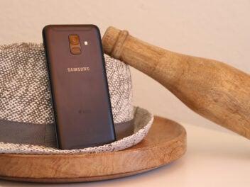 Samsung Galaxy A6 auf einem Hut und mit einer Holzflasche
