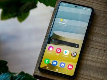 Das Samsung Galaxy A72 auf einem Holzuntergrund mit aktivem Display.