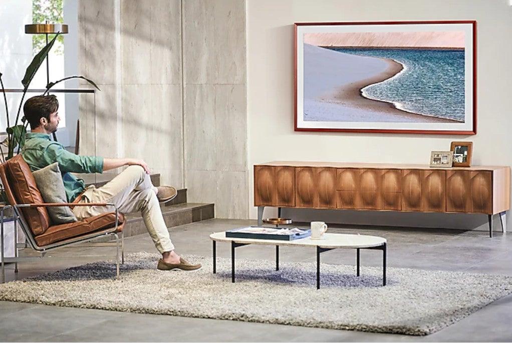 Ein TV als Gemälde verkleidet hängt an der Wand über einem Sideboard, ein Mann schaut darauf.