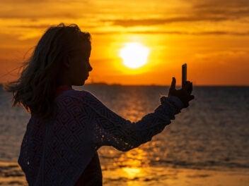 Junges Mädchen fotografiert sich selbst am Meer