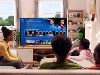 Familie schaut Sky auf einem Sofa vor dem Fernseher.