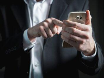 Ein Mann im Anzug benutzt ein Smartphone