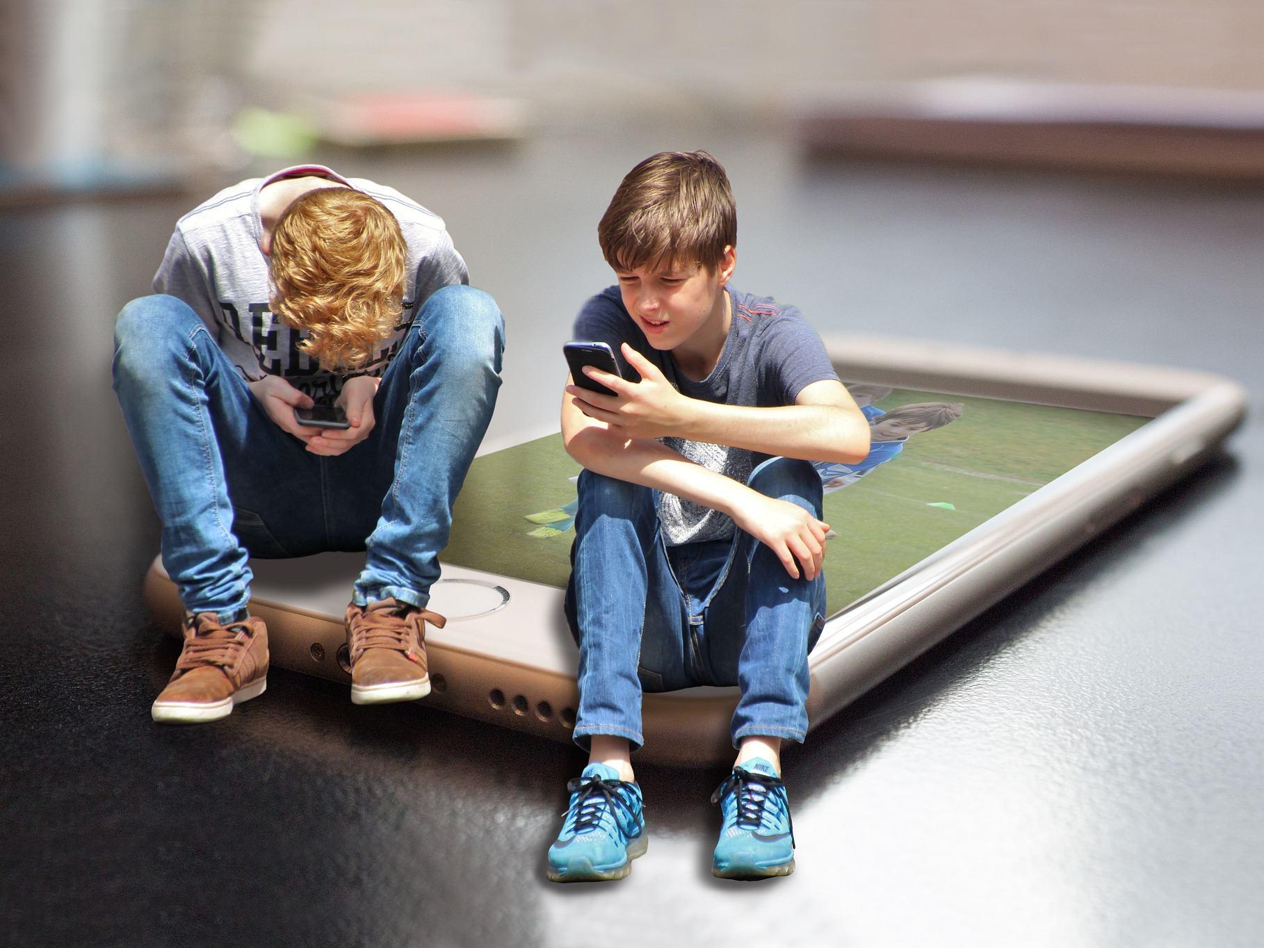 Zwei Kinder nutzen Smartphones, dabei sitzen sie symbilisch auf einem übergroßen Smartphone