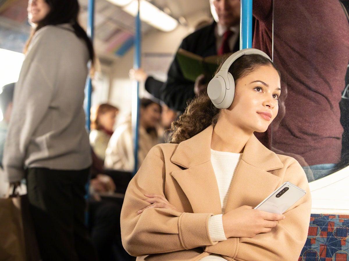 Eine Frau trägt die Sony Over-Ear-Kopfhörer WH-1000XM4