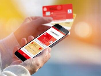 Die Sparkassen-App zum mobilen Bezahlen auf einem Handy, daneben zwei Sparkassen-Karten.