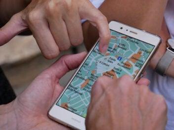 Mehrere Hände zeigen auf eine Navi-App auf einem Handy