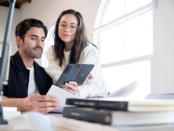 Ein Mann zeigt einer Frau etwas auf dem Microsoft Surface Duo 2 Smartphone