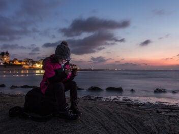 Frau sitzt im Winter am Strand und surft auf ihrem Smartphone