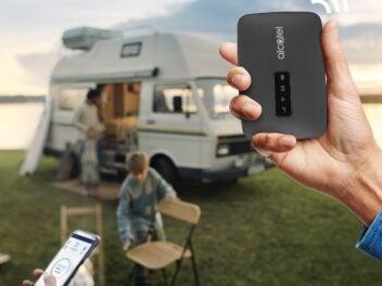 Ein mobiler WLAN-Hotpspot, im Hintergrund ein Wohnmobil und eine Familie