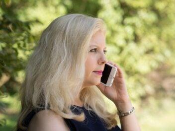 Eine blonde Frau telefonieren im Wald mit dem Handy