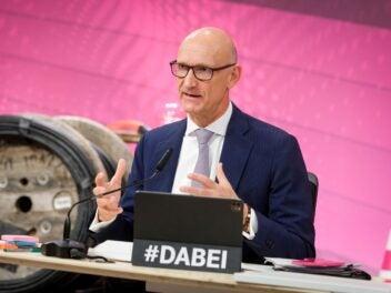 Telekom-Chef Tim Höttges hält seine Rede zur Bilanzpressekonferenz sitzen am Tisch, im Vordergrund sein Tablet mit dem Schriftzug #Dabei