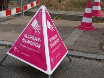 Ein Warnschild vor einer Glasfaser-Baugrube der Telekom
