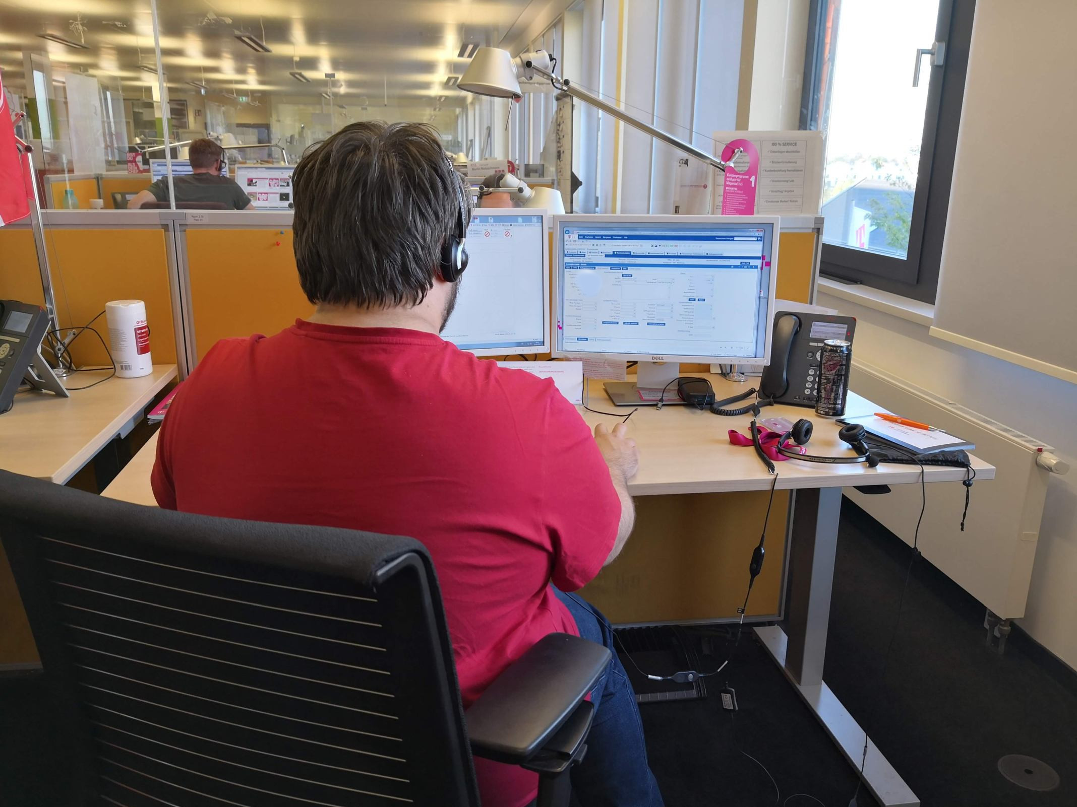 Ein Service-Mitarbeiter der Telekom sitzt an seinem Arbeitsplatz, er ist von hinten zu sehen und hat ein Headset auf.