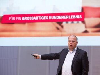 Telekom-Deutschland-Chef Dirk Wössner beim Partnergipfel 2019 vor der Schrift Für ein großartiges Kundenerlebnis