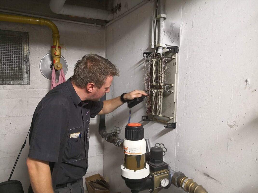 Ein Telekom-Techniker arbeitet am APL, dem Übergabepunkt im Wohnhaus zwischen Telekom-Netz und Wohnhaus