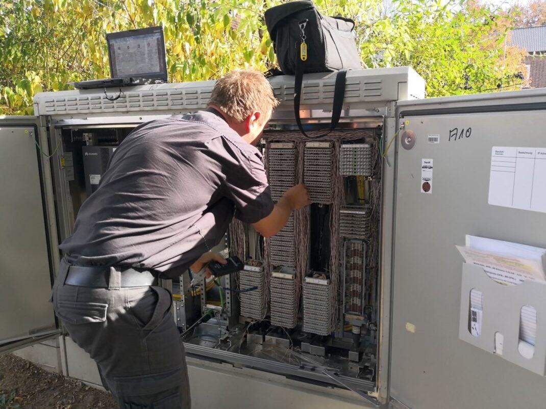 Ein Telekom-Techniker arbeitet am Multifunktionsgehäuse
