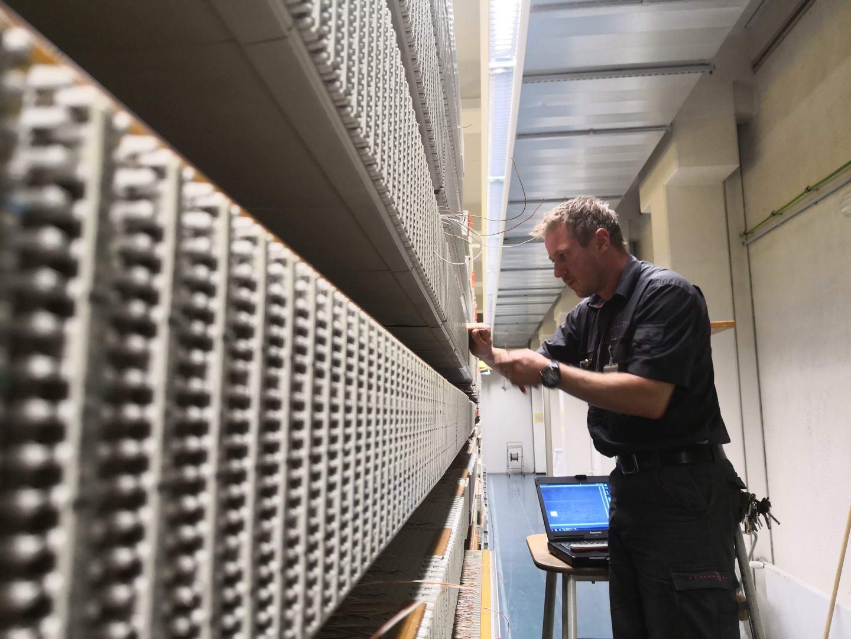 Ein Telekom-Techniker arbeitet in einer Vermittlungsstelle