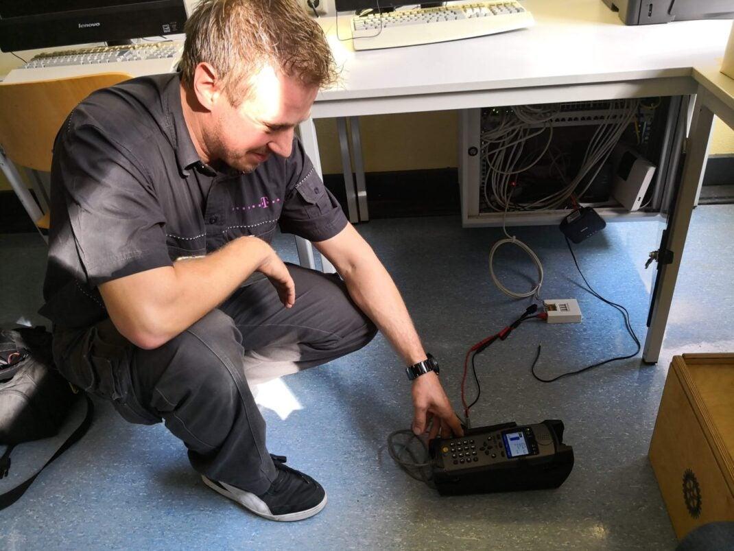 Ein Telekom-Techniker mit einem Messgerät prüft einen Telefonanschluss