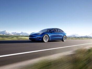 Tesla Model 3 in Blau fährt auf der Straße vor einer Berglandschaft.