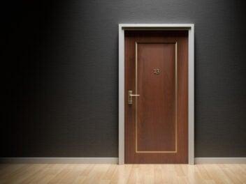 Eine dunkle Holztür mit der Nummer 13