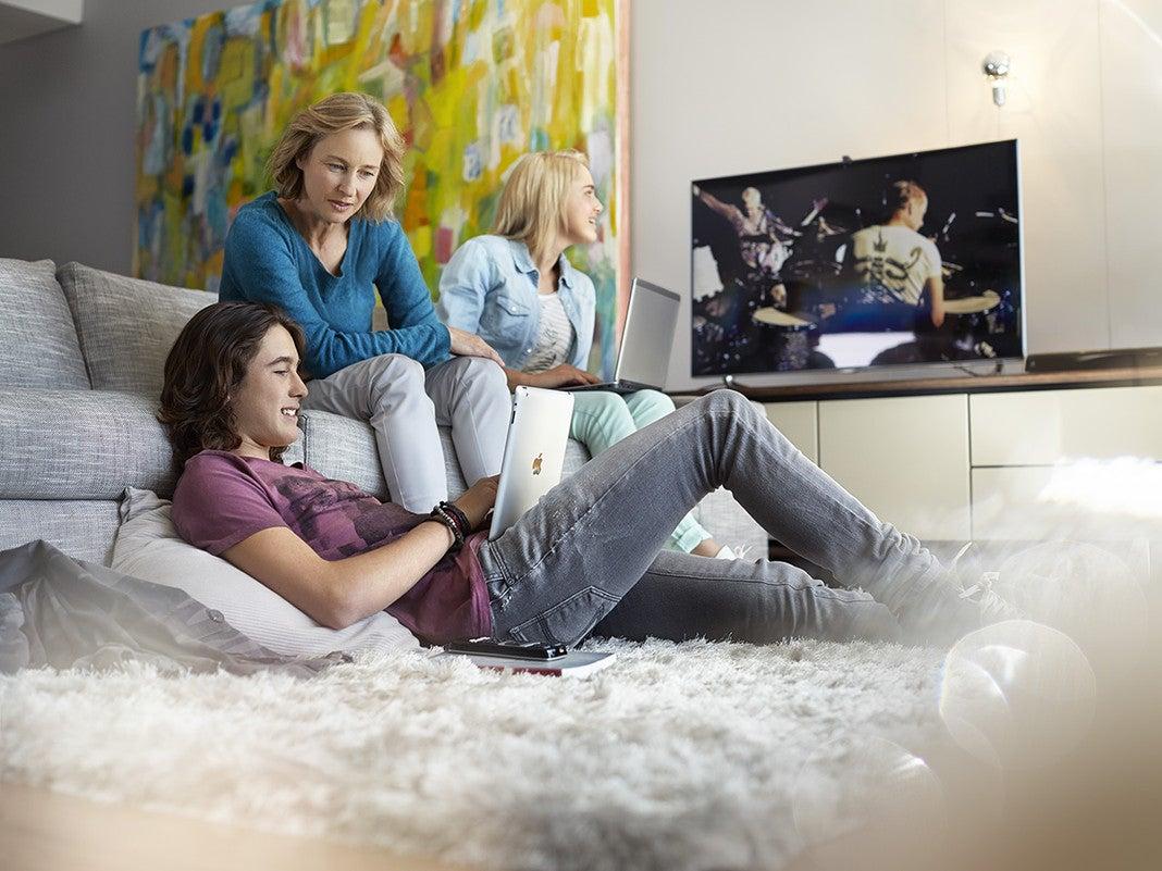 Mutter und Kinder surfen im Netz und sehen dabei Fern