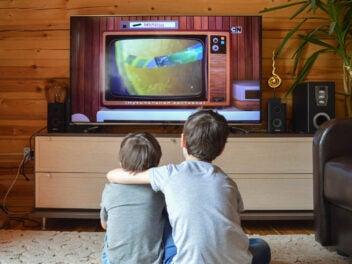 Zwei Jungs sehen sich Cartoons im Fernsehen an