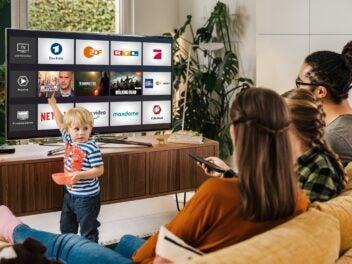 Eine Familie sitzt auf der Couch vor einem Fernseher, auf dem TV-Streaming-Dienste zu sehen sind.