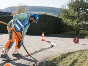 Glasfaser-Ausbau bei Unitymedia: Ein Bauarbeiter verlegt Speedpipes in der Straße