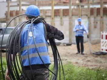 Ein Techniker mit Unitymedia-Weste trägt Glasfaser-Leerrohre zu einer Baustelle