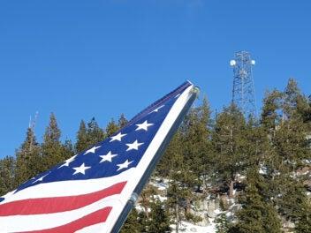 USA-Flagge und Mobilfunkmast