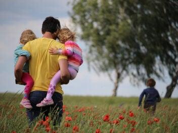 Ein Vater trägt zwei Kinder auf dem Arm, eines läuft vornweg durch ein Mohnblumenfeld
