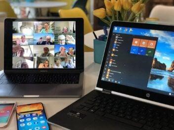 Zwei Laptops und ein zwei Handys in einer Homeoffice-Situation mit einer Videokonferenz