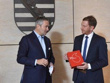 Vodafone-Chef Ametsreiter und Ministerpräsident Krtschmer vor dem Wappen Sachsens