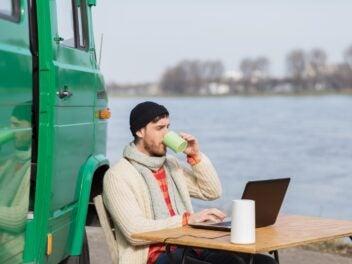 Ein Man sitzt an einem Fluß an einem Campingtisch und nutzt den Vodafone GigaVube