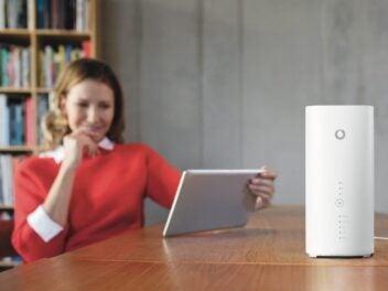 Der Vodafone GigaCube Premium steht auf einem Tisch, links sitzt eine Frau mit einem Tablet